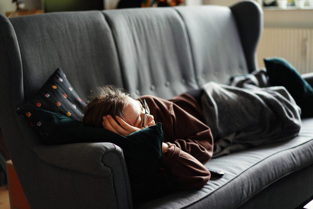 6時間しか眠っていないせいで仕事中に眠たくなってしまう男性のイメージ