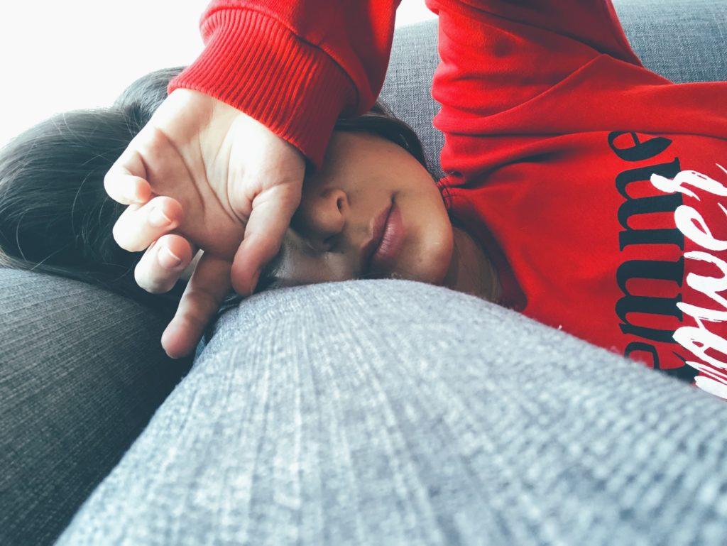 ソファーで横になり休む女性