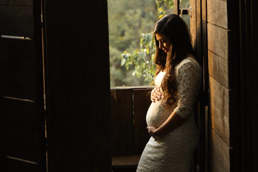 立ってお腹を支える妊婦