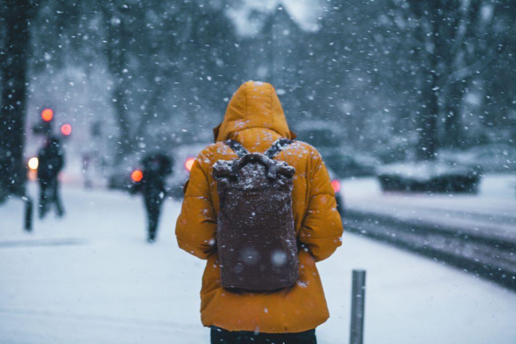 雪の中厚着して歩く人