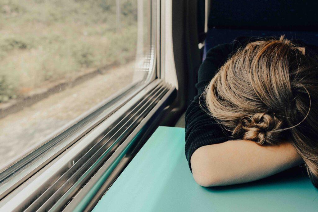 電車で酔ってしまいつらくてうつ伏せになっているイメージ