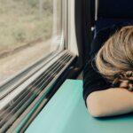 電車で乗り物酔いになってしまいうつ伏せになっているイメージ