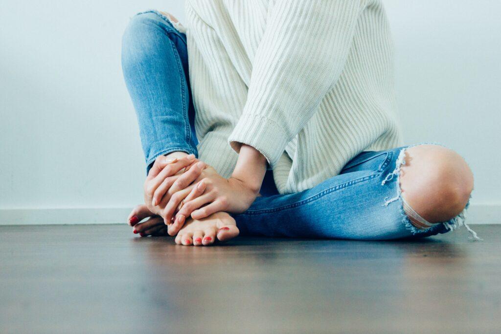 足がむくんでいるのでマッサージして和らげているイメージ